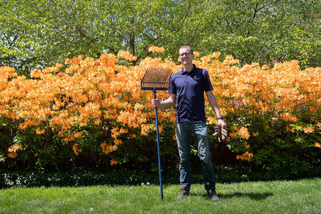 Evan Hershey holding a rake in front of some flowers