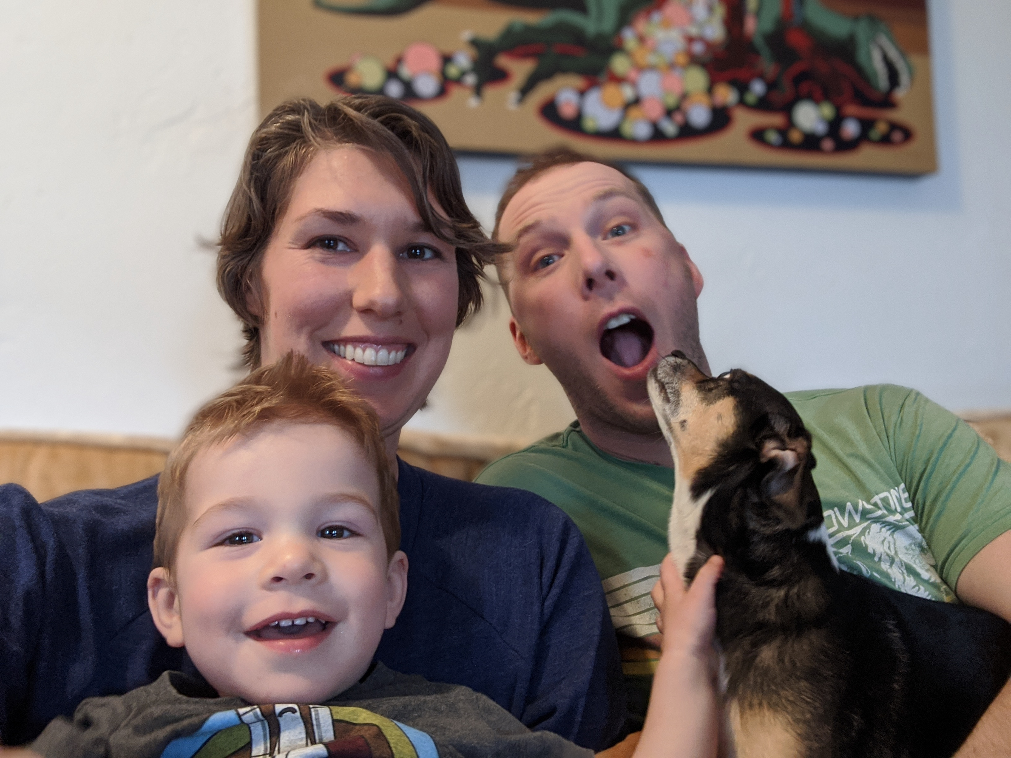Photo family of three slightly interrupted by dog