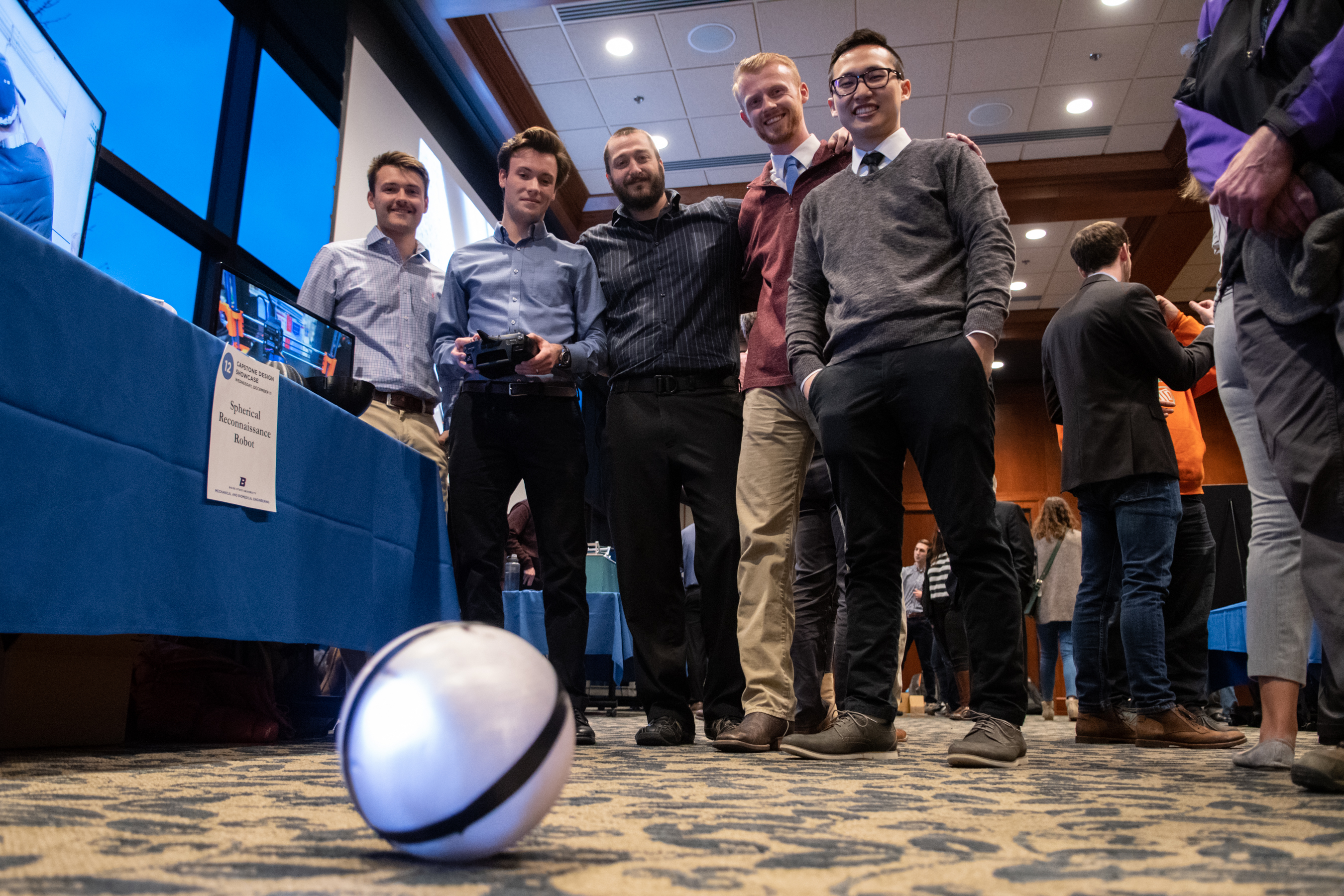 Team of students look down at spherical robot on ground