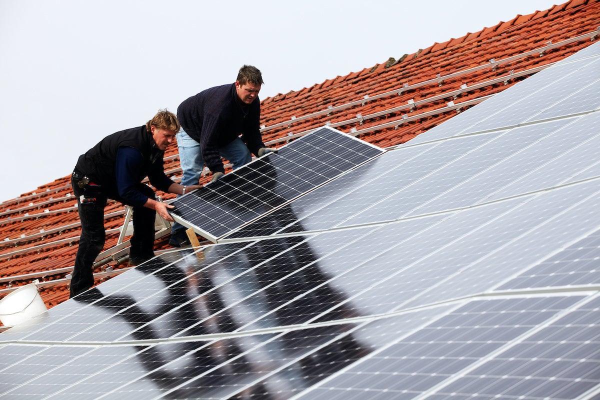 men installing solar cells on roof