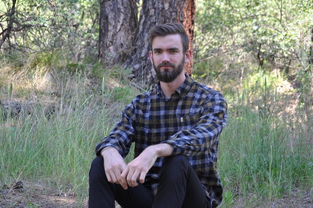 Aaron sitting in woodlands