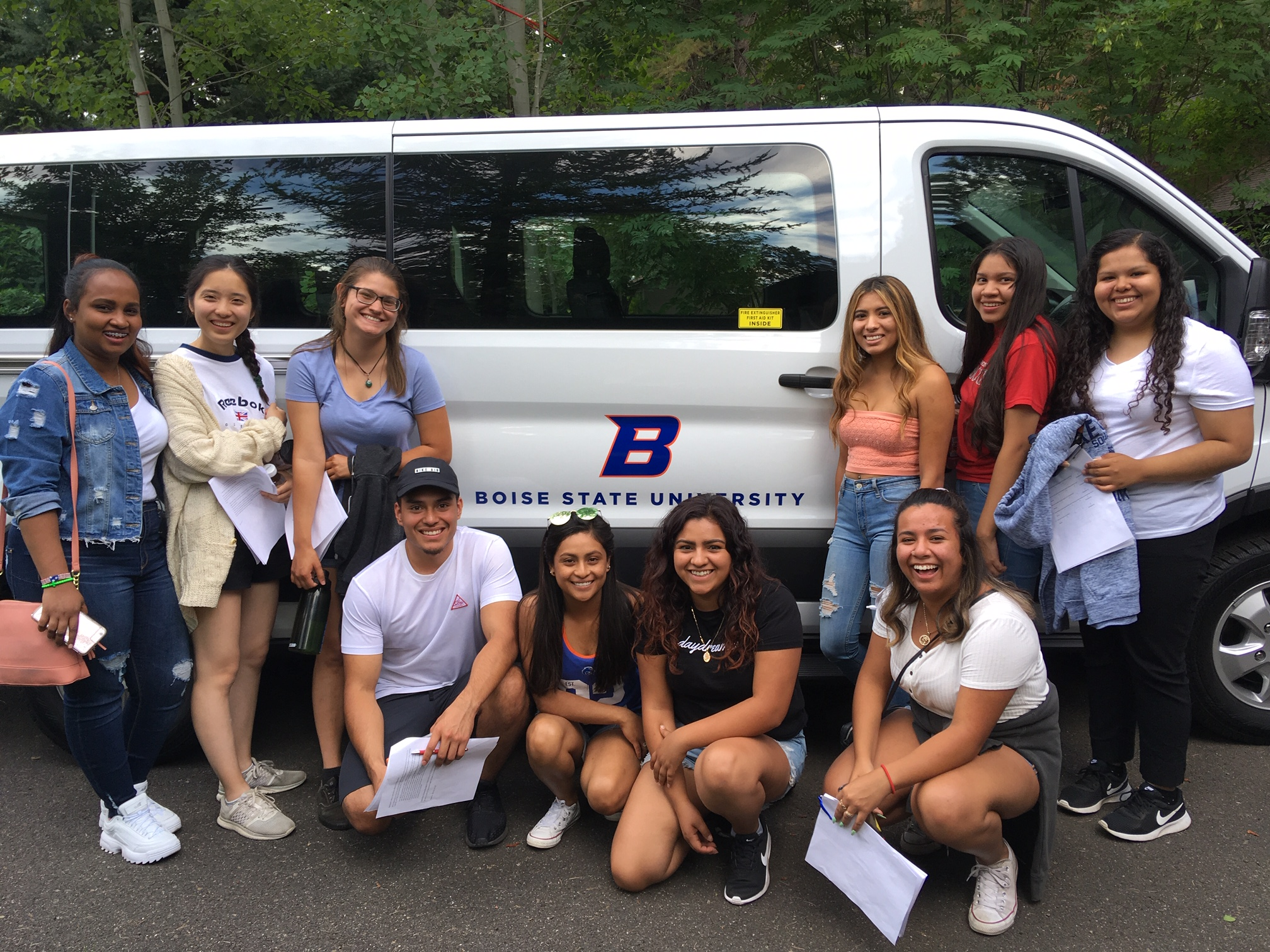 TRIO students pose near a van
