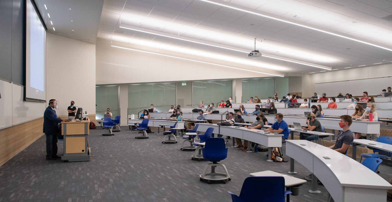View of a lecture hall inside the building, everyone is wearing masks and professor has a face shield as well