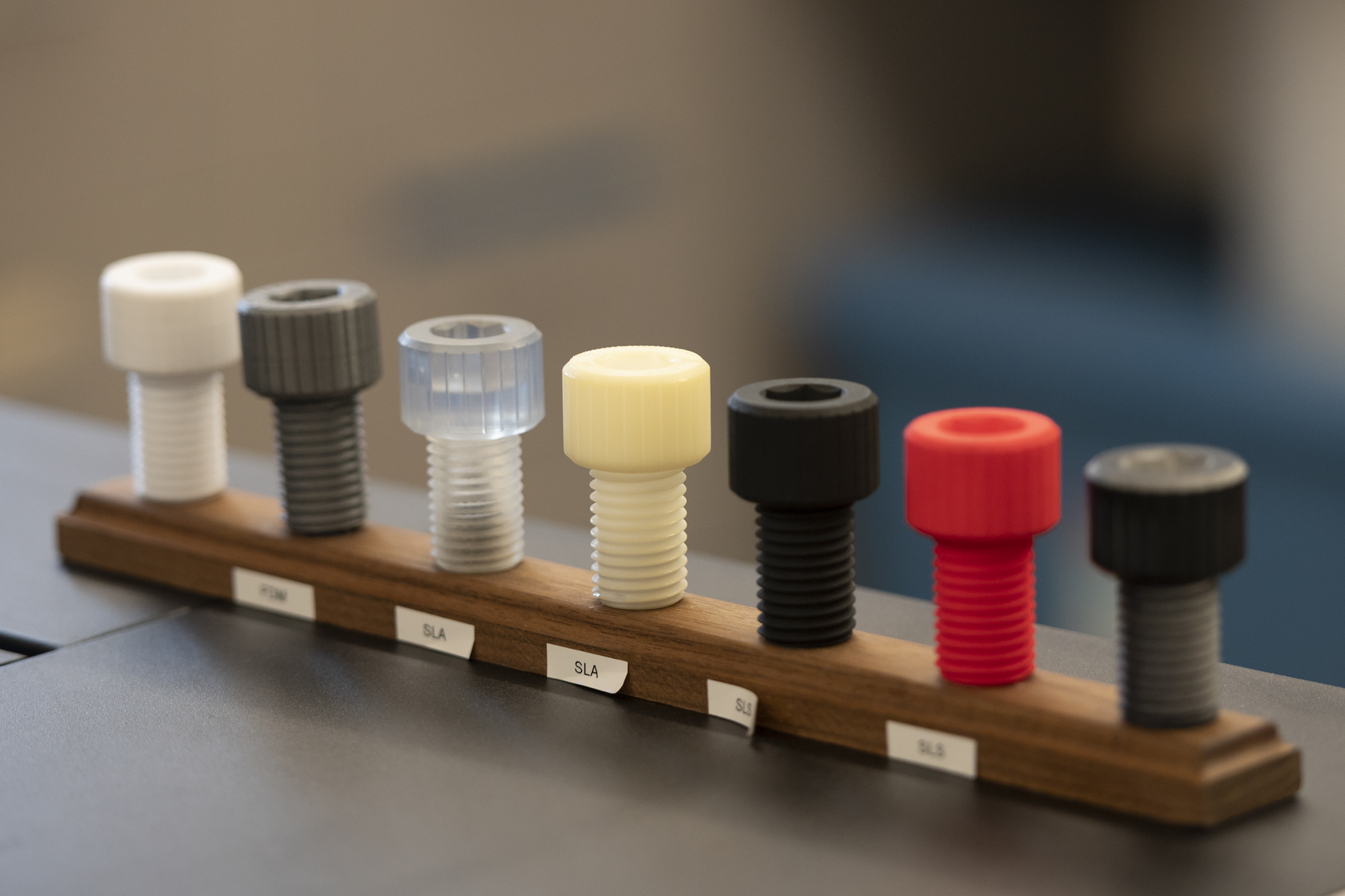 A line-up of 7 screws made out of different materials.