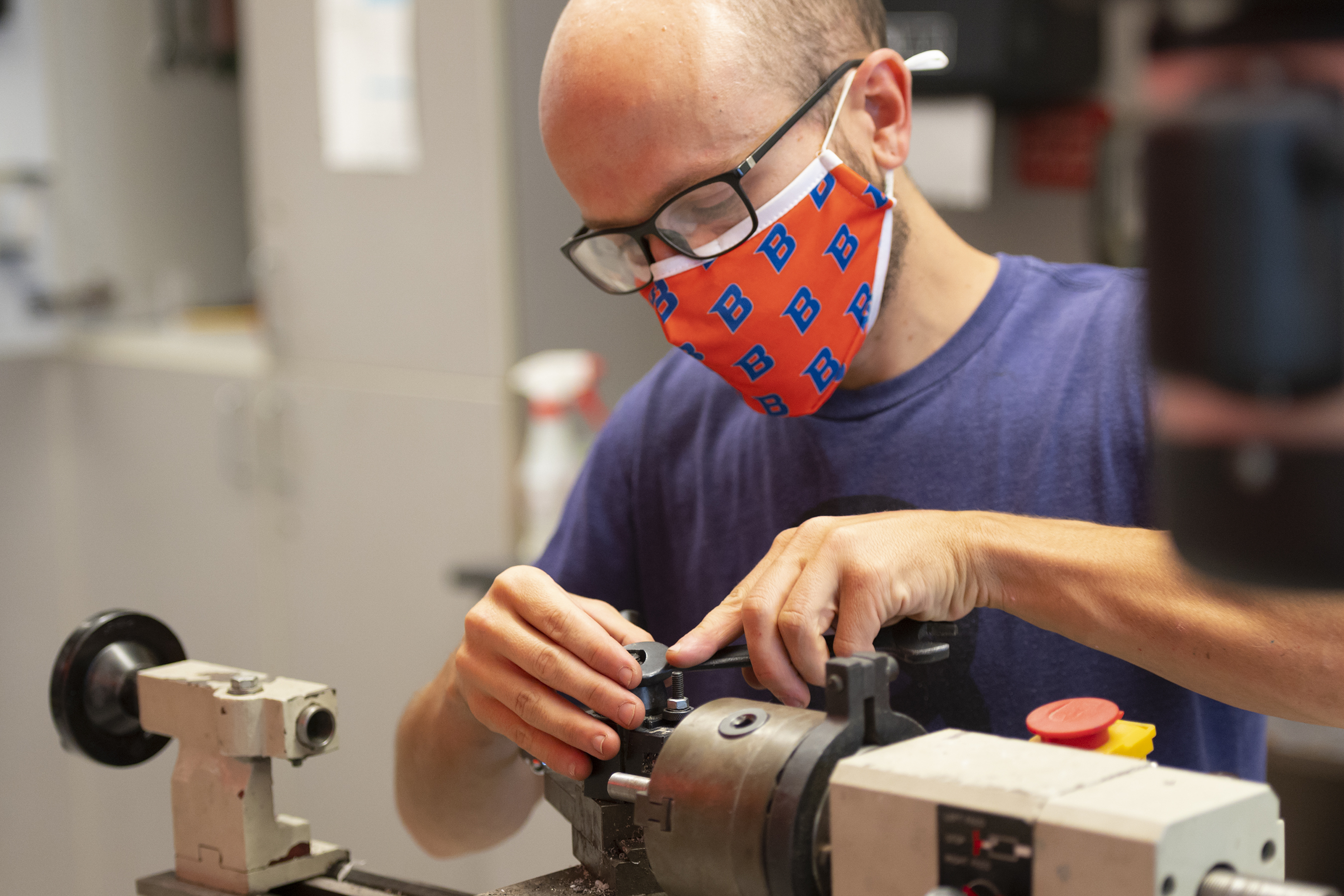 Student wearing a BSU mask works with lab equipment, holding a wrench