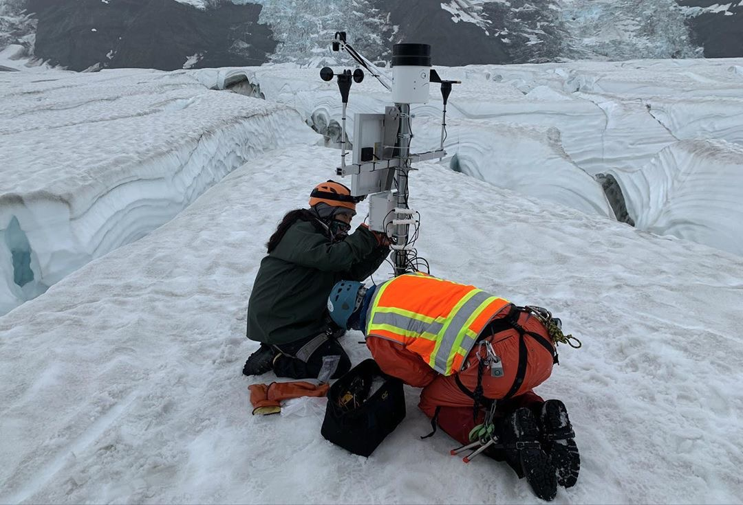 two people install weather in glacier ice