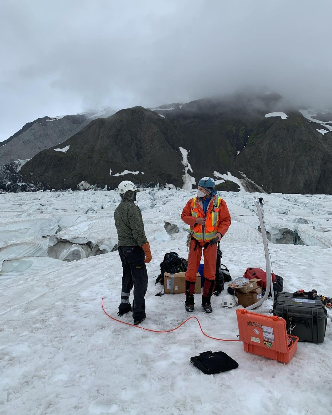 researchers surrounded by equipment, standing on glacier