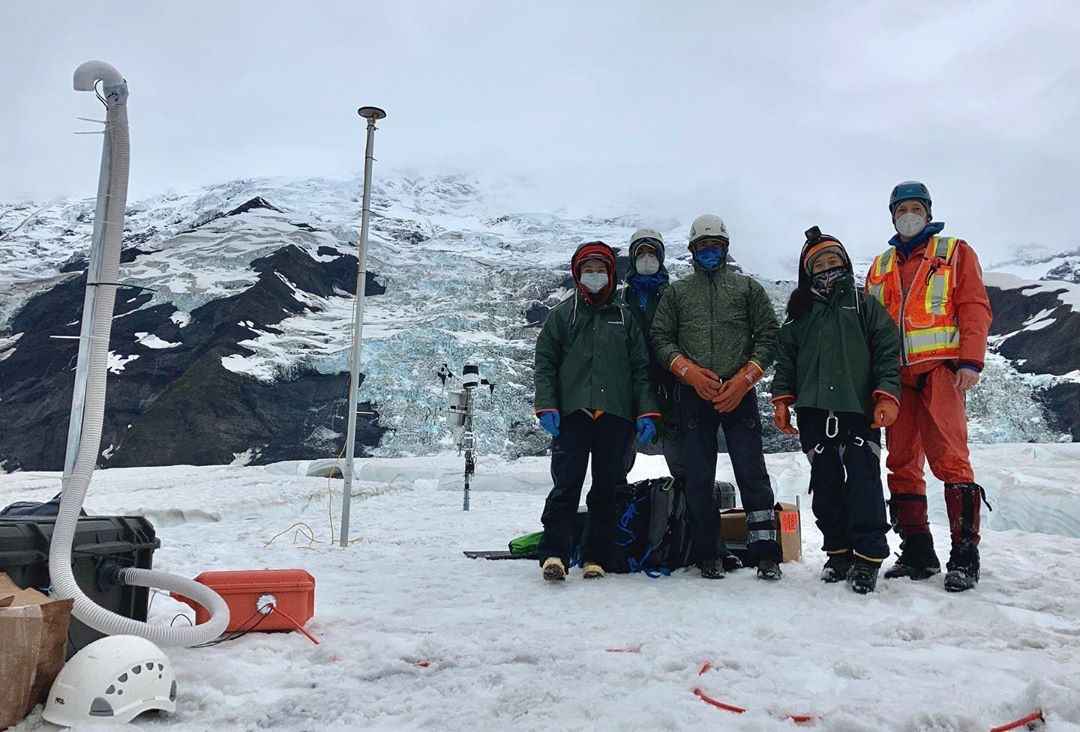 group of researchers pose on glacier