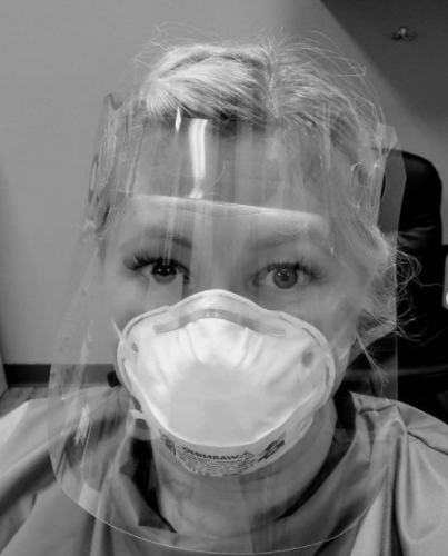Melanie Kanawyer wears a clear face shield, face mask, and protective overshirt to prevent fluid contamination.