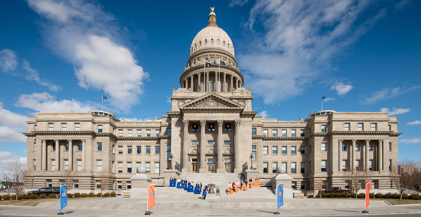 Students stand with Boise State flags and letters in front of Idaho state Capitol building