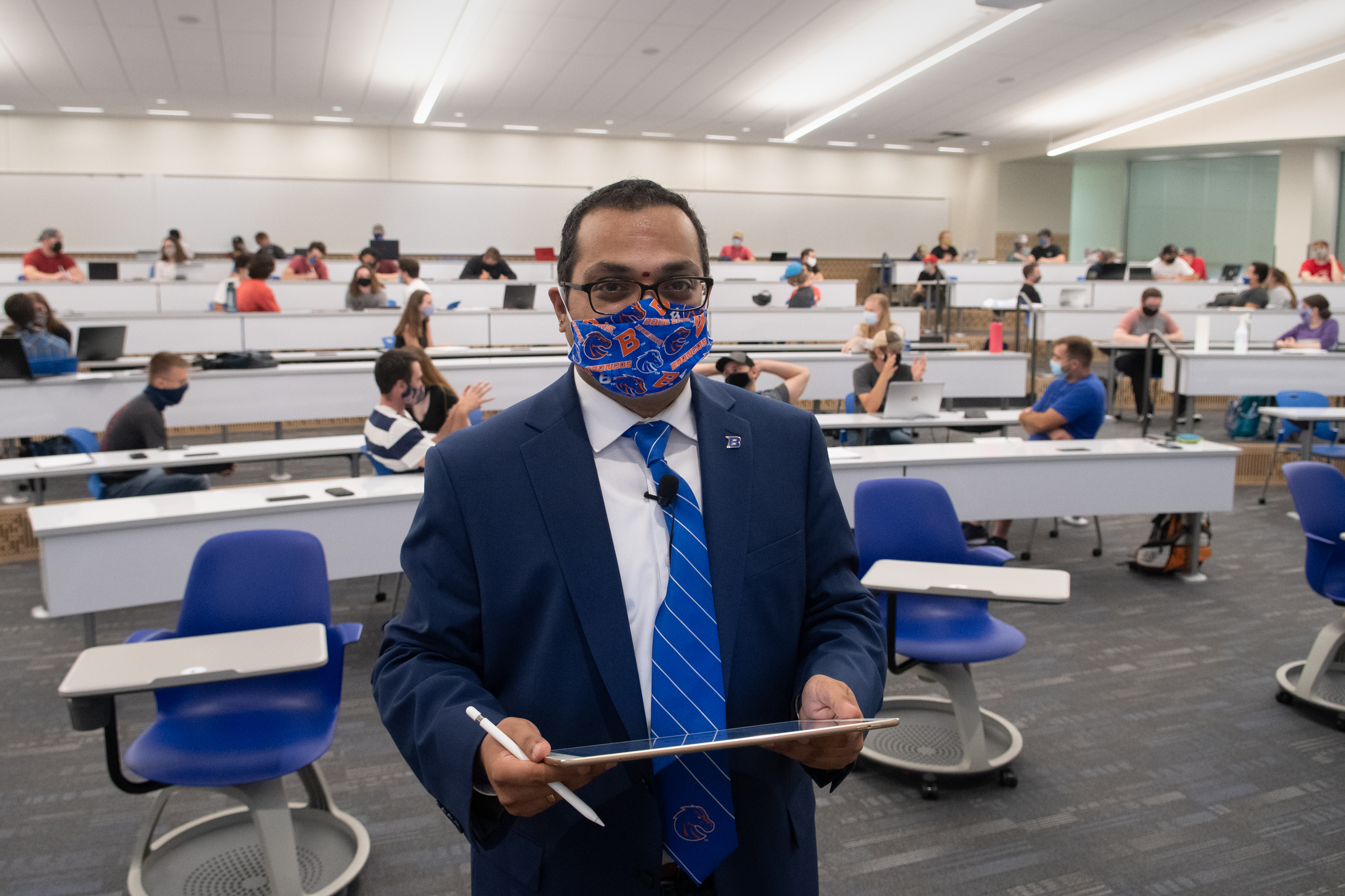krishna wears mask, his back to auditorium full of socially distanced, mask-wearing students