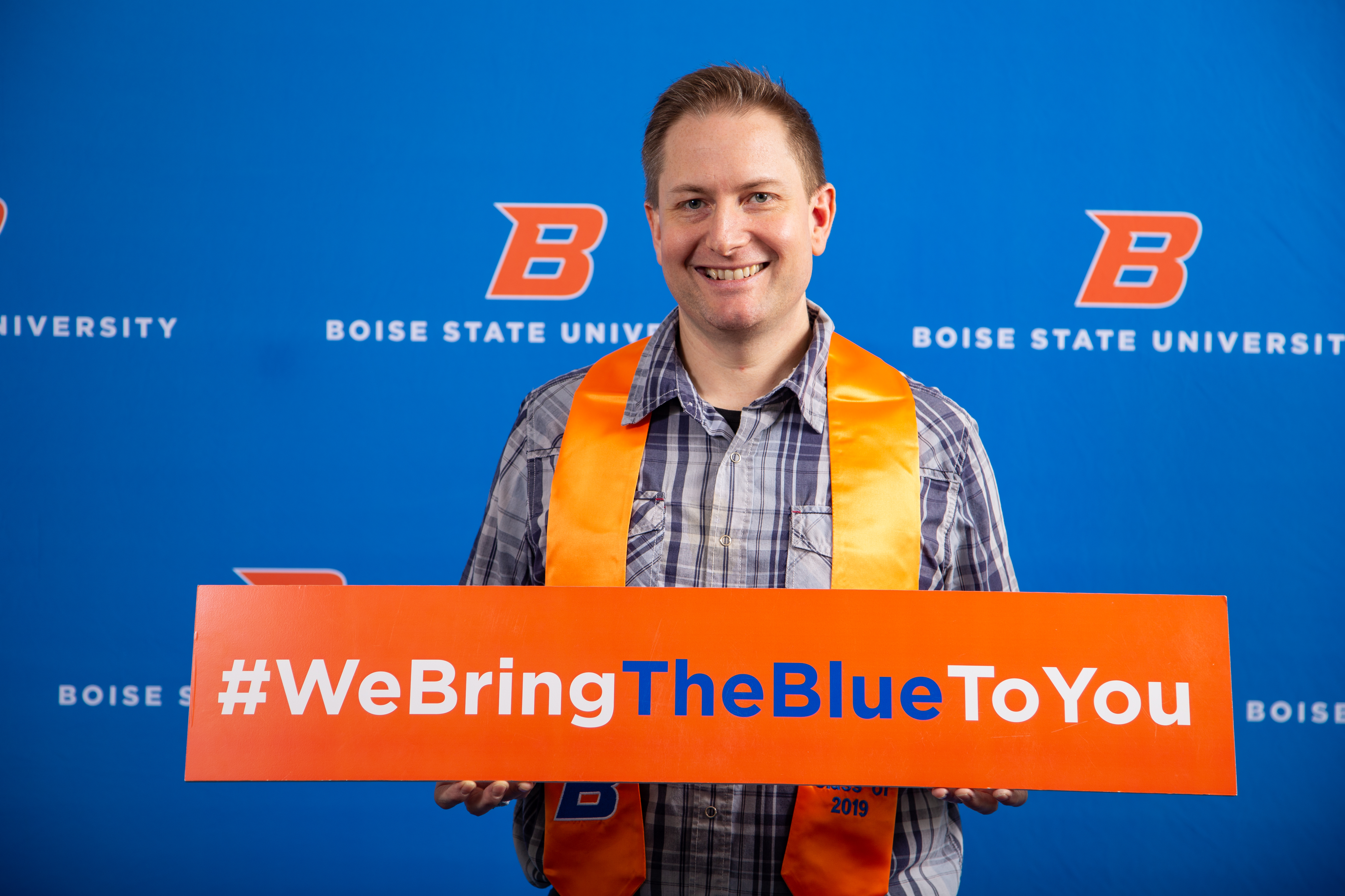 """Student holds a sign reading """"We Bring The Blue To You."""""""