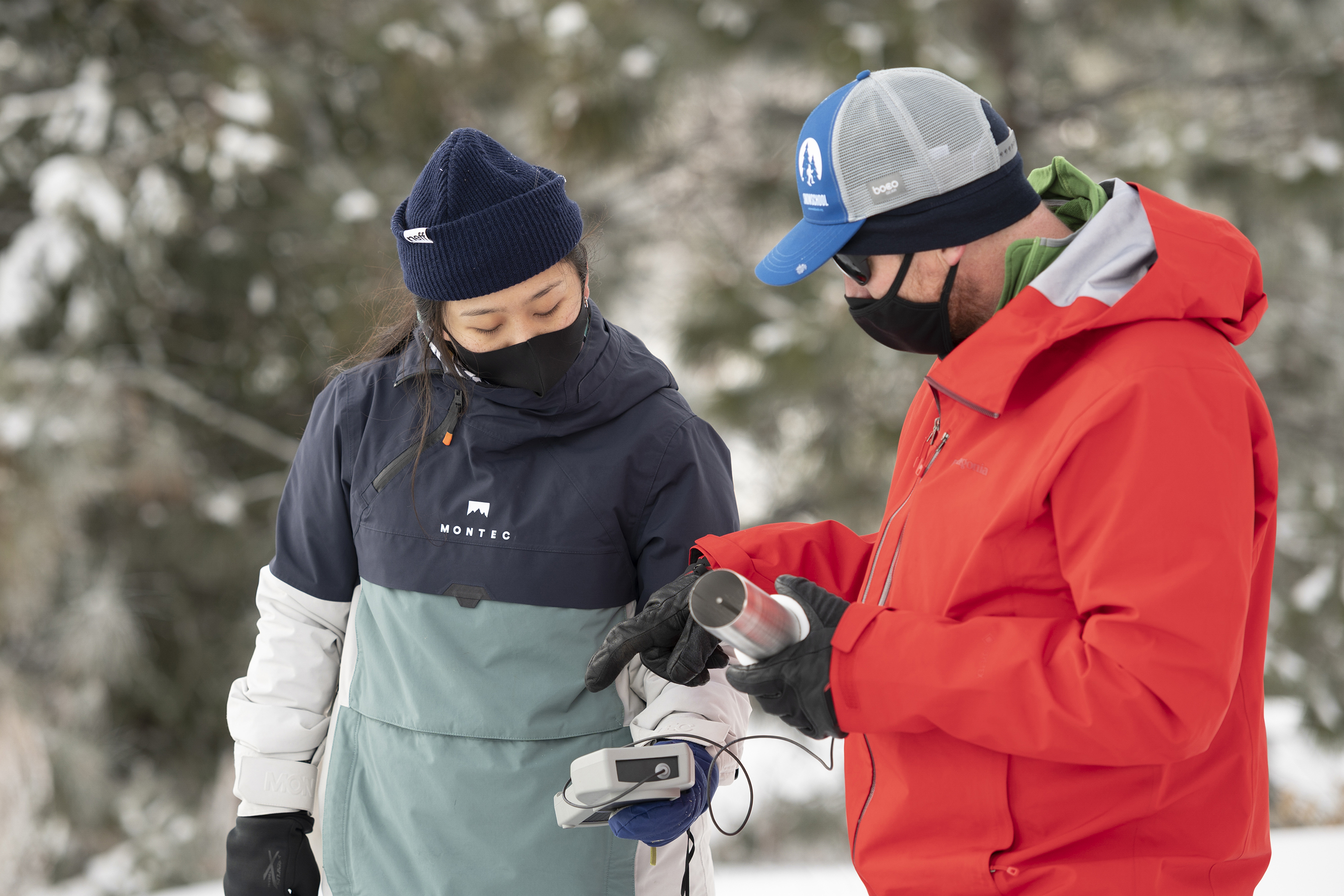 student and teacher look at device in snow