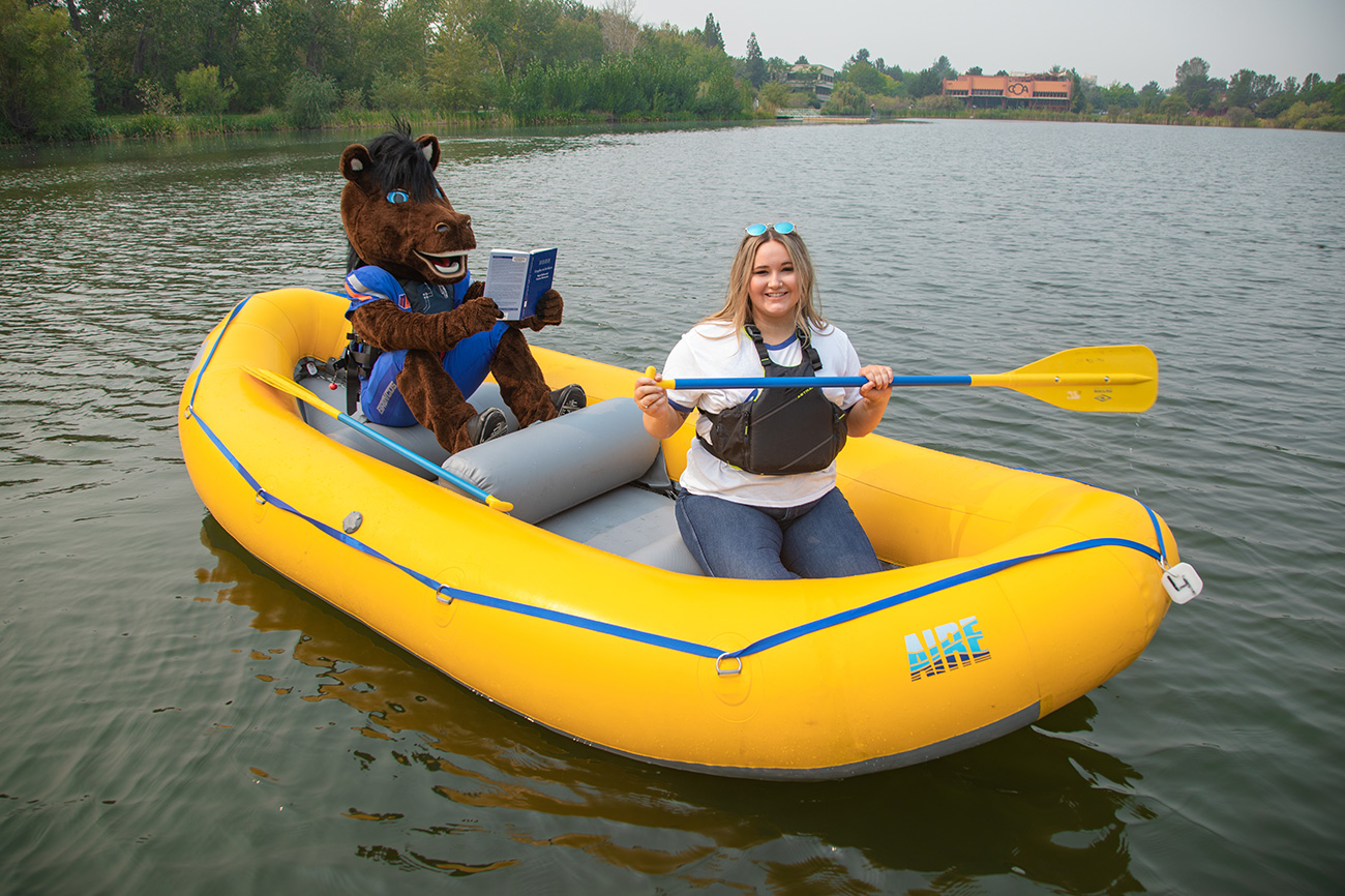Student and Buster Bronco in a raft.