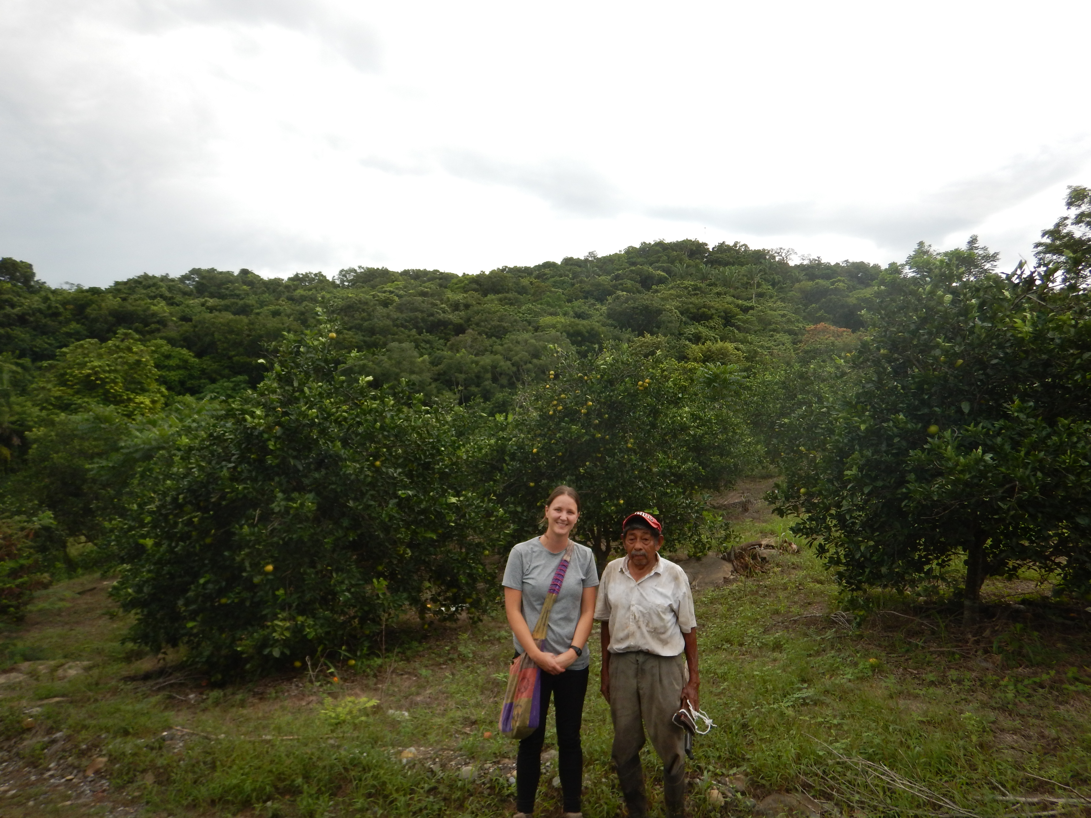 Paige and elderly man in front of vanilla plants