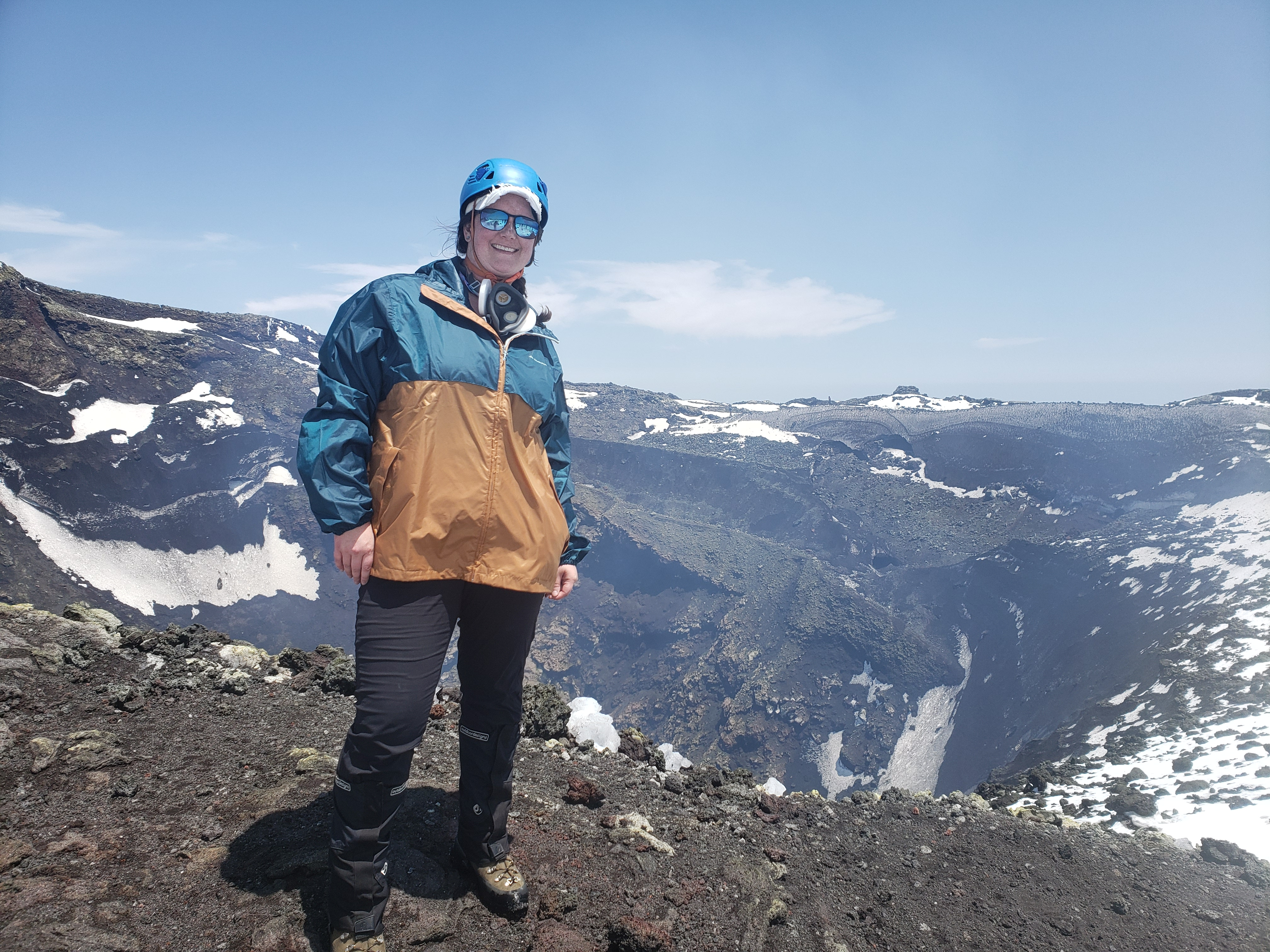 woman stands near top of volcano