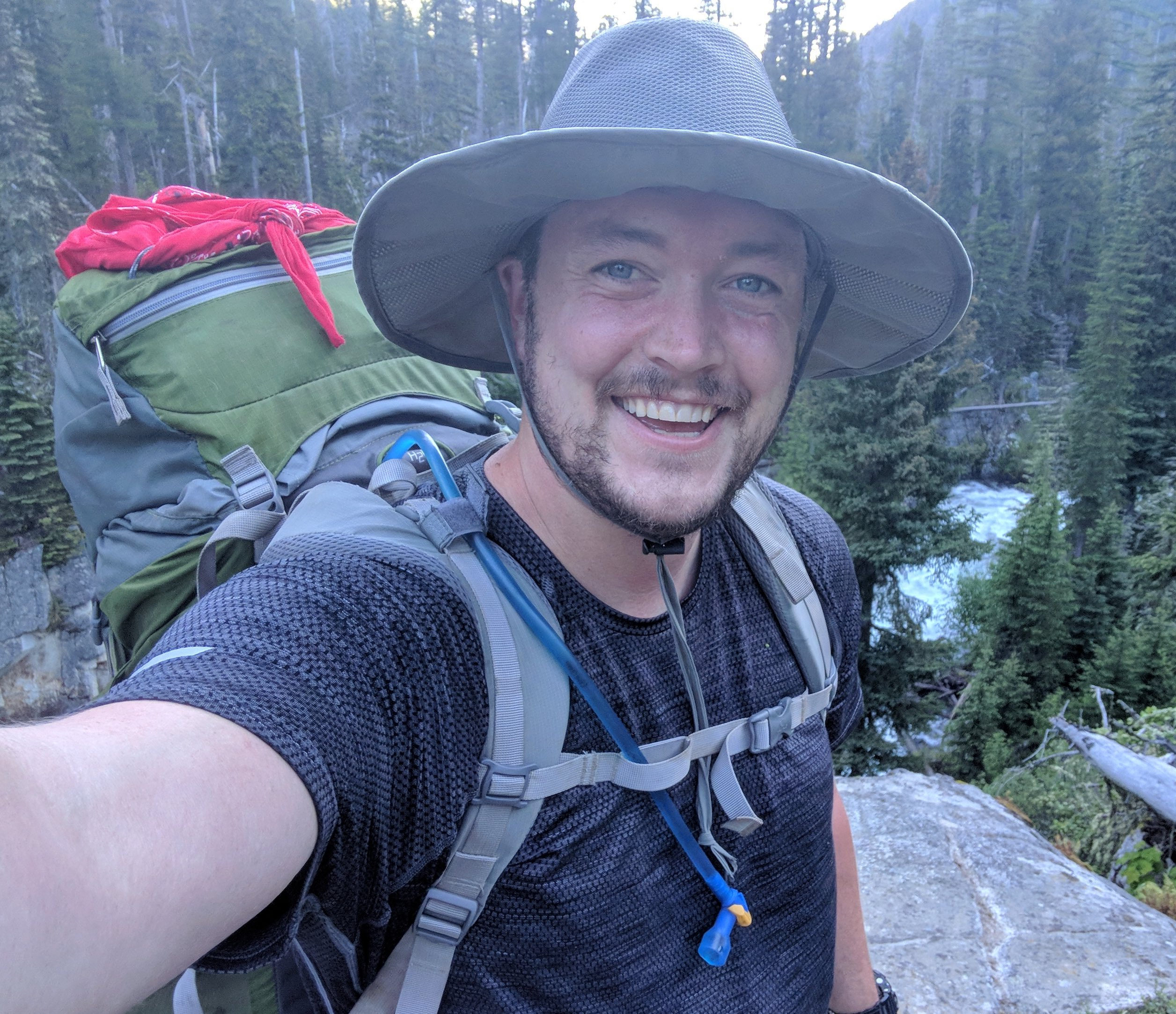 man in woods wearing hiking gear and hat