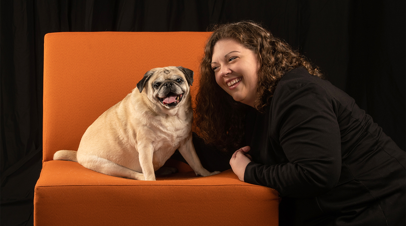 Shelly Volsche and her dog, Lucy on an orange chair