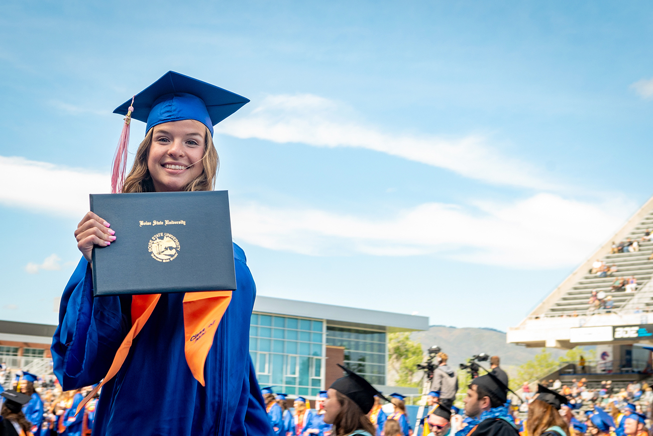 Student holding diploma at outdoor commencement ceremony
