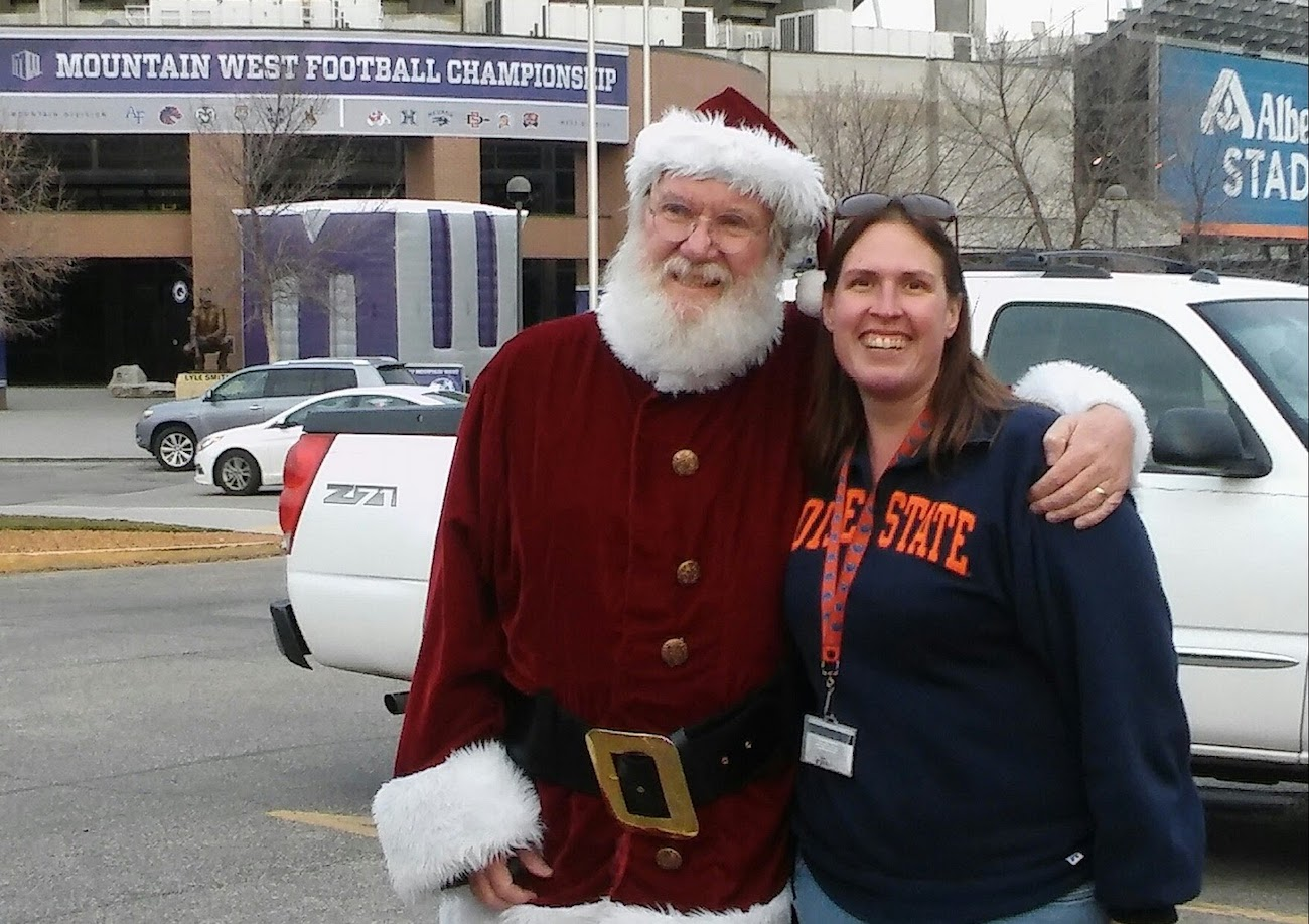 A woman poses for a photo with Santa Claus