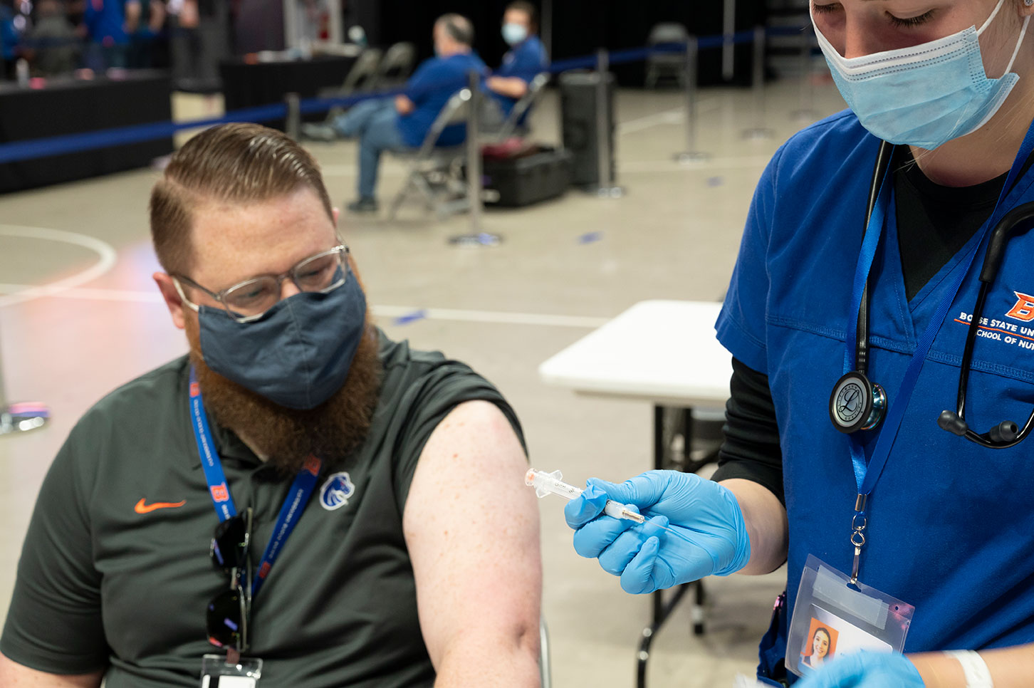Nursing student prepares to give a vaccine at Boise State COVID mass vaccination clinic, Extra Mile Arena, April 3, 2021