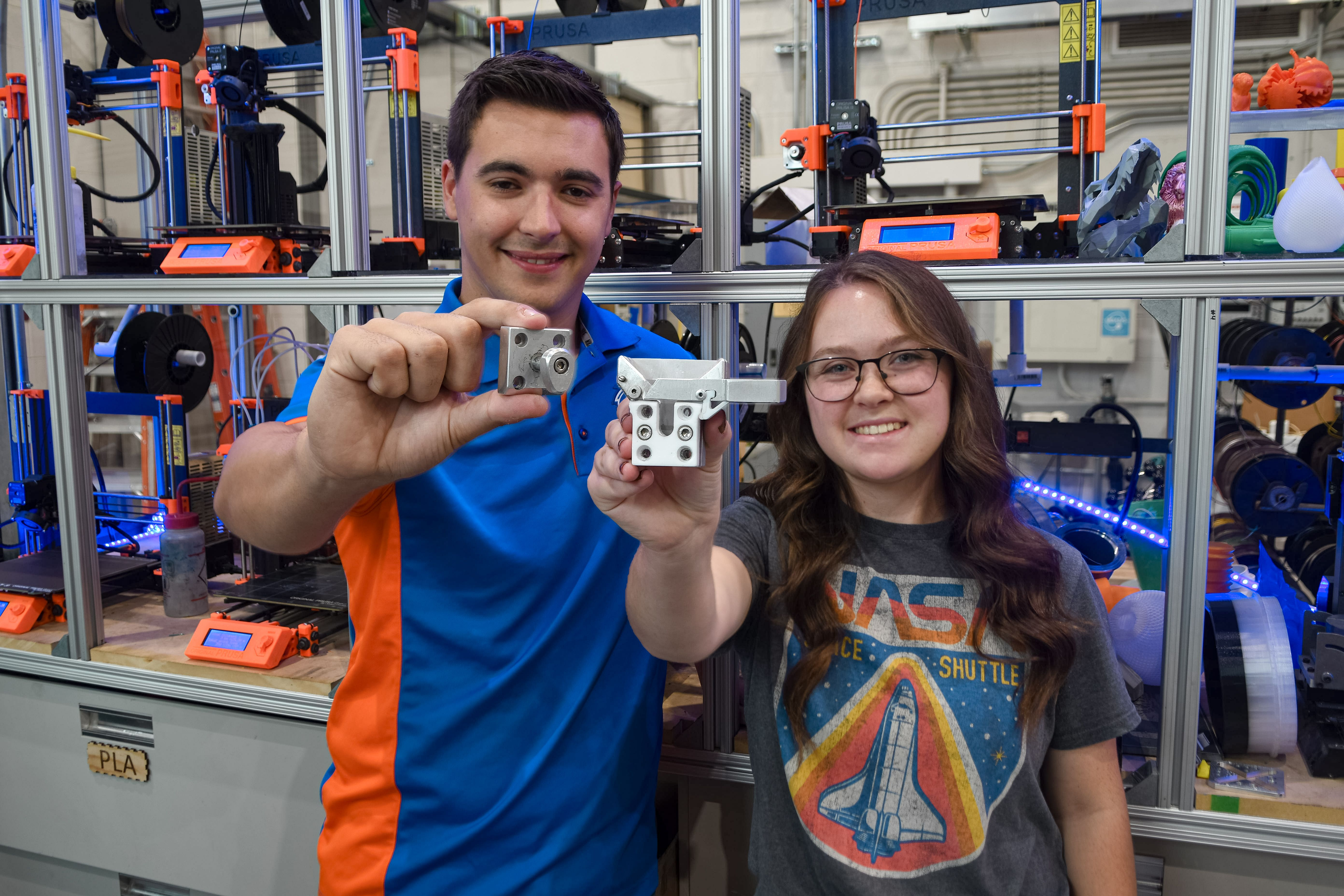 Two people in workshop holding 3D printed plastic pieces