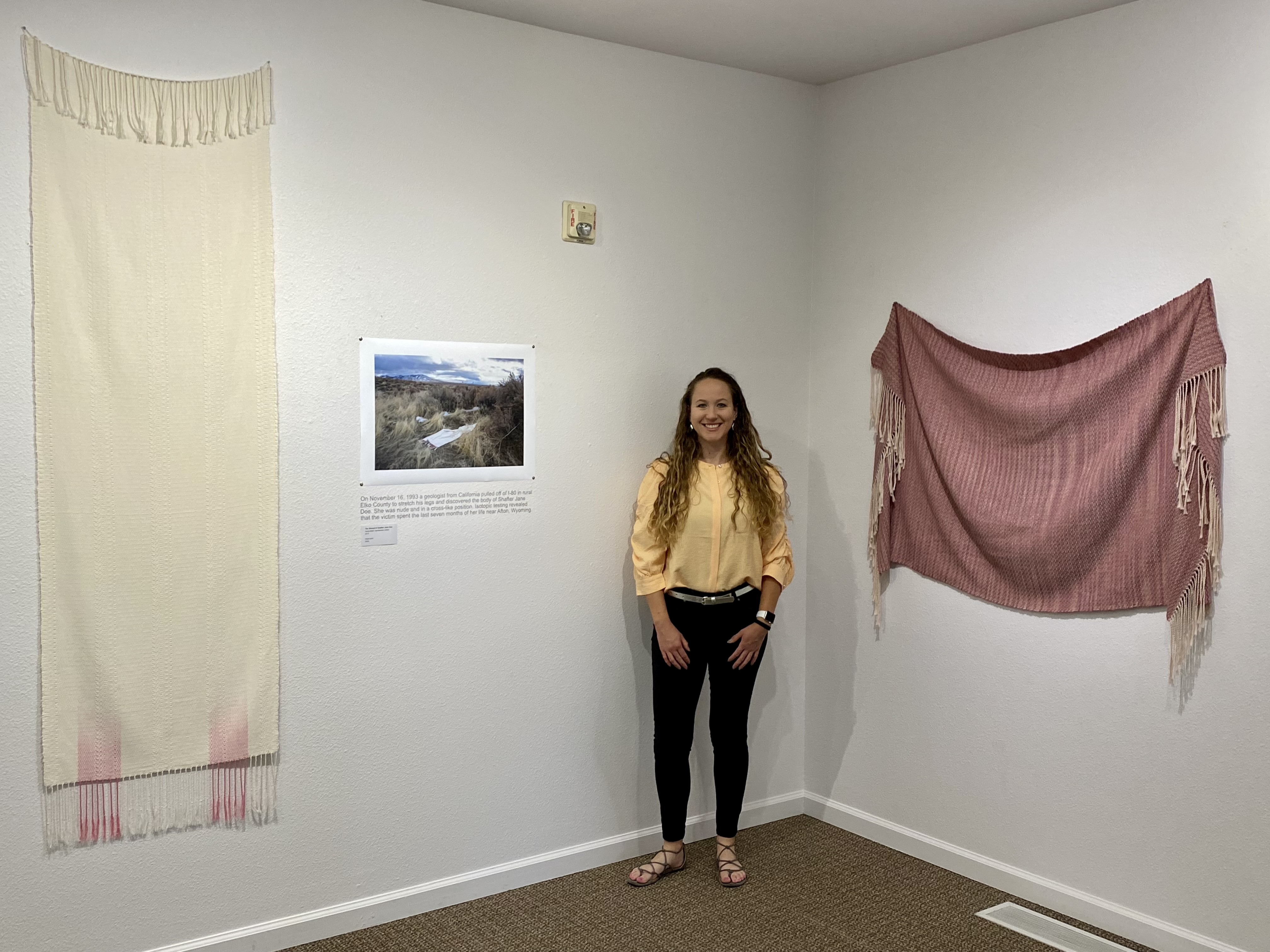 woman stands in museum exhibit surrounded by hanging woven shrouds