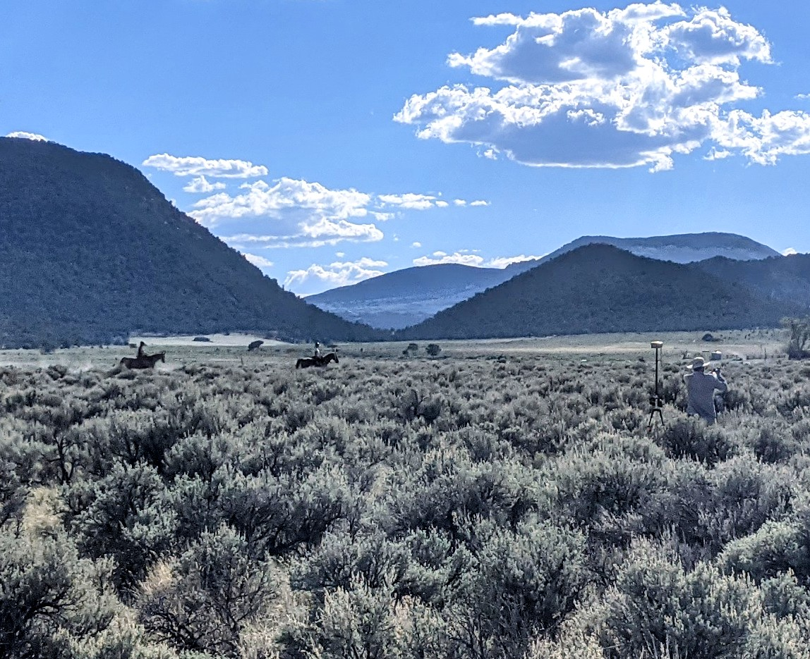 people riding horses across sagebrush steppe, mountains in distance