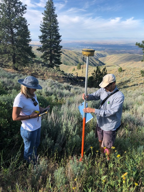 two people stand in sagebrush steppe with research equipment