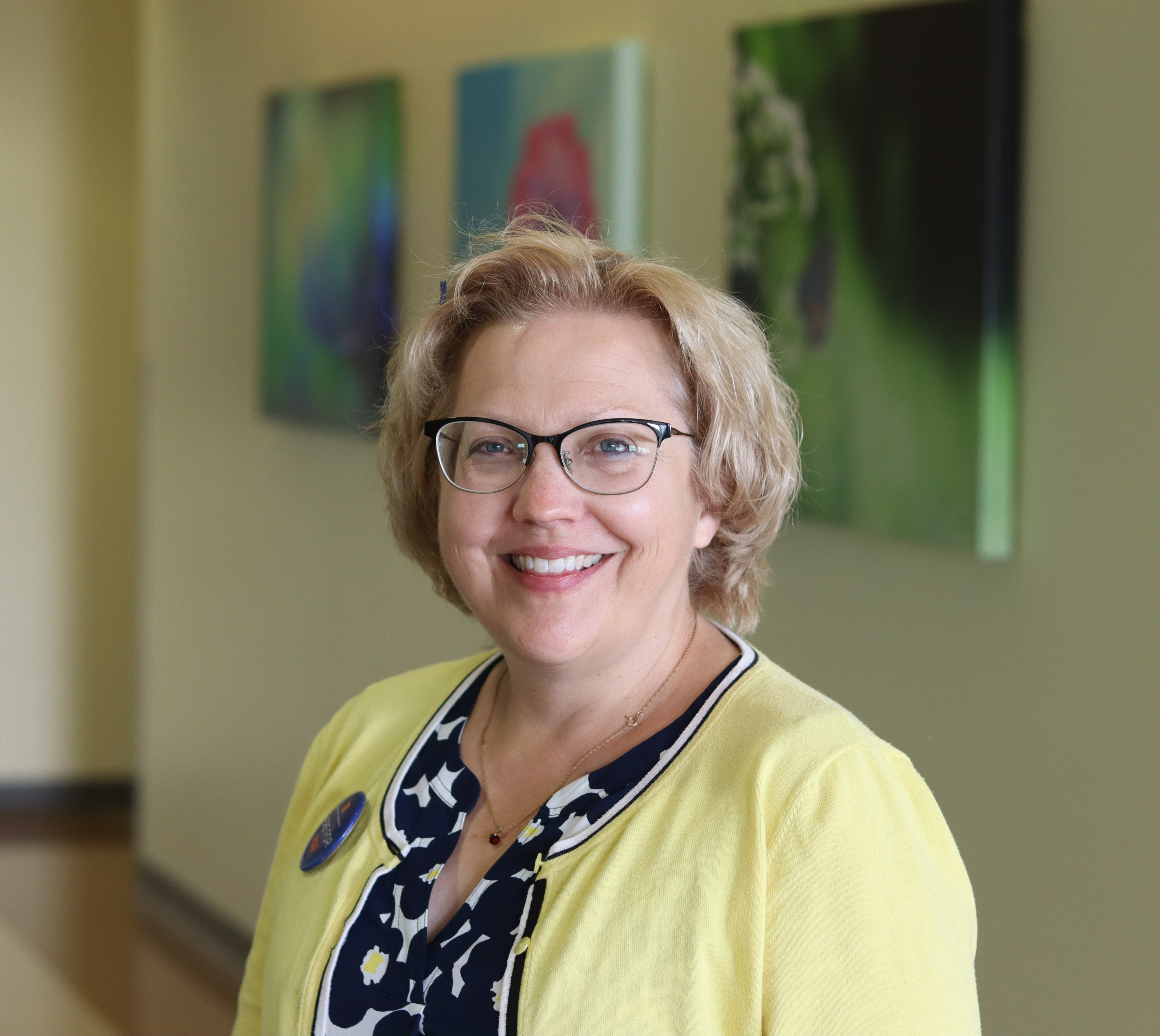 Amy Spurlock's headshot. She is standing in a hallway at the School of Nursing, looking at the camera and smiling.