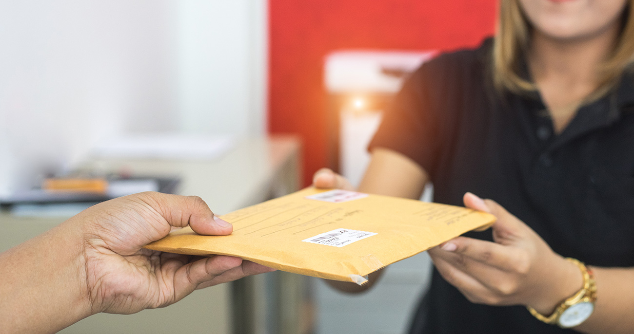 Person handing a mail delivery to another person