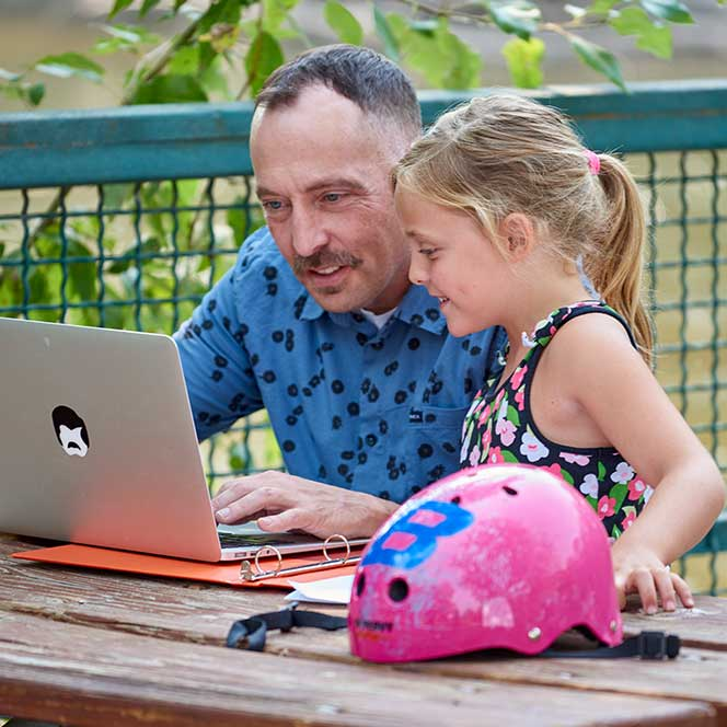 A man looks at his laptop with his daughter.