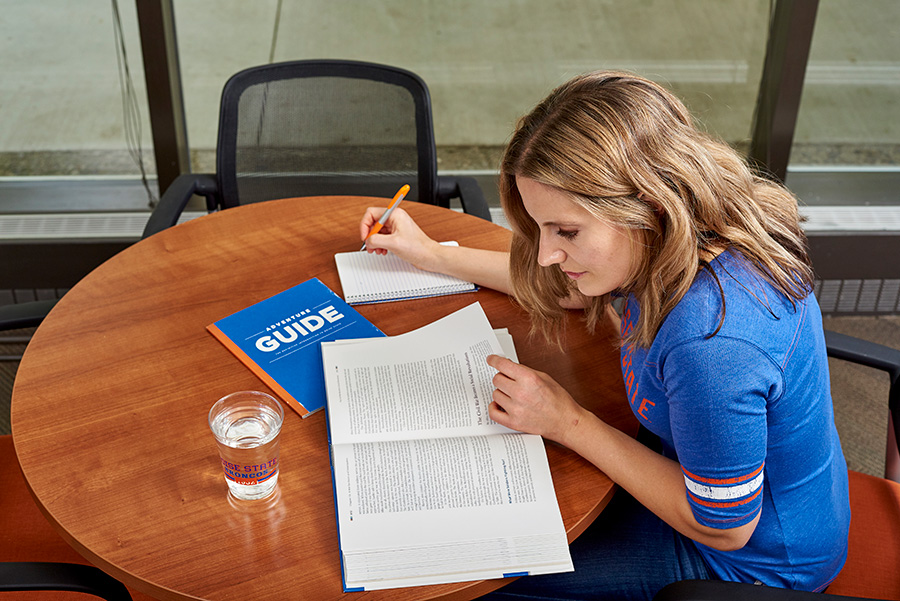 Woman at table studying textbook