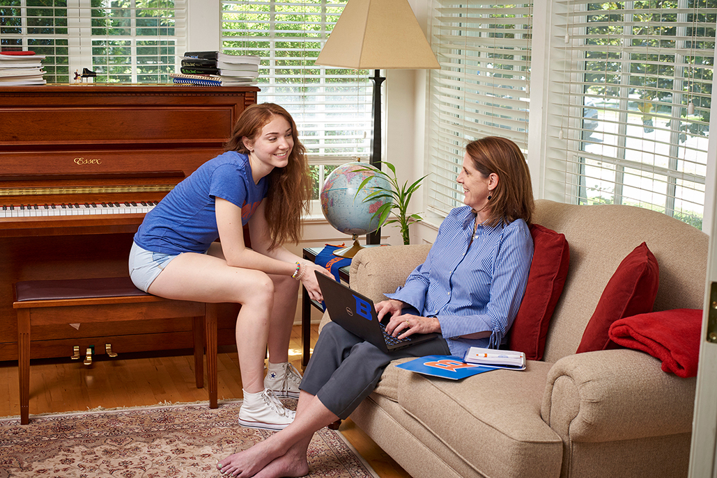 MSA Student at home with daughter. Sitting on couch with laptop.