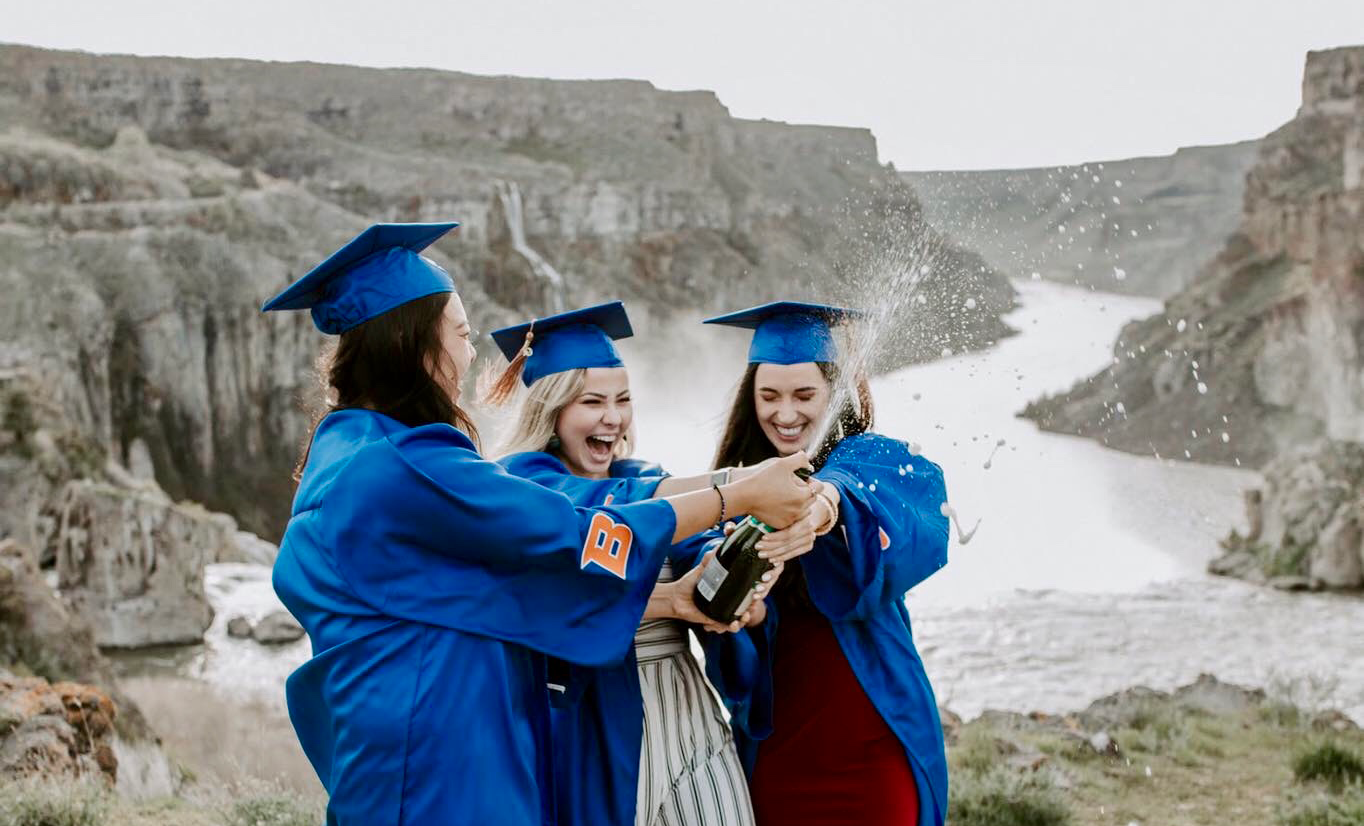 Ervina and her friends pop a bottle of champagne to celebrate graduation, wearing Boise State Graduation gowns.