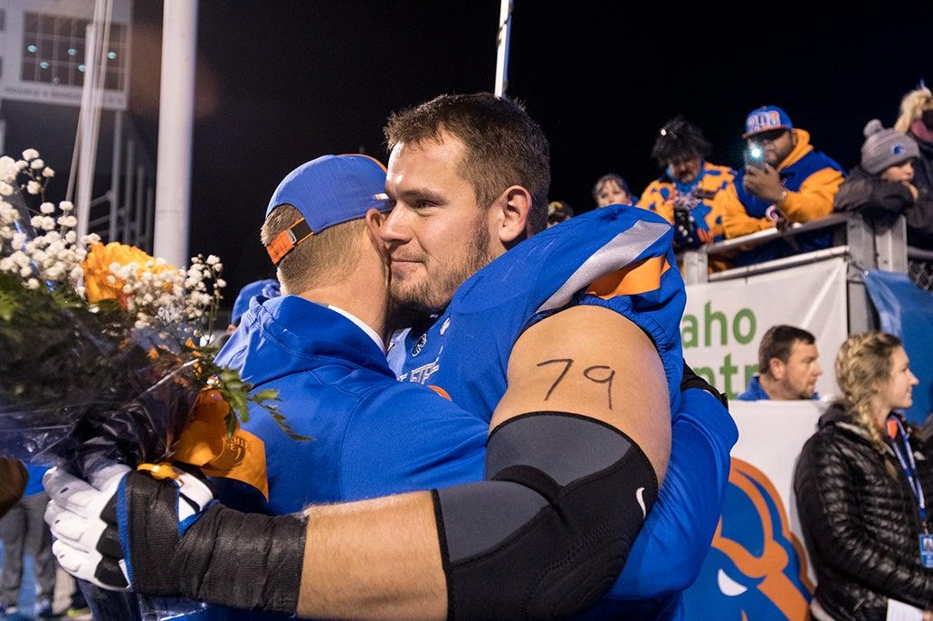 Mason Hampton dressed in football uniform, hugging coach.