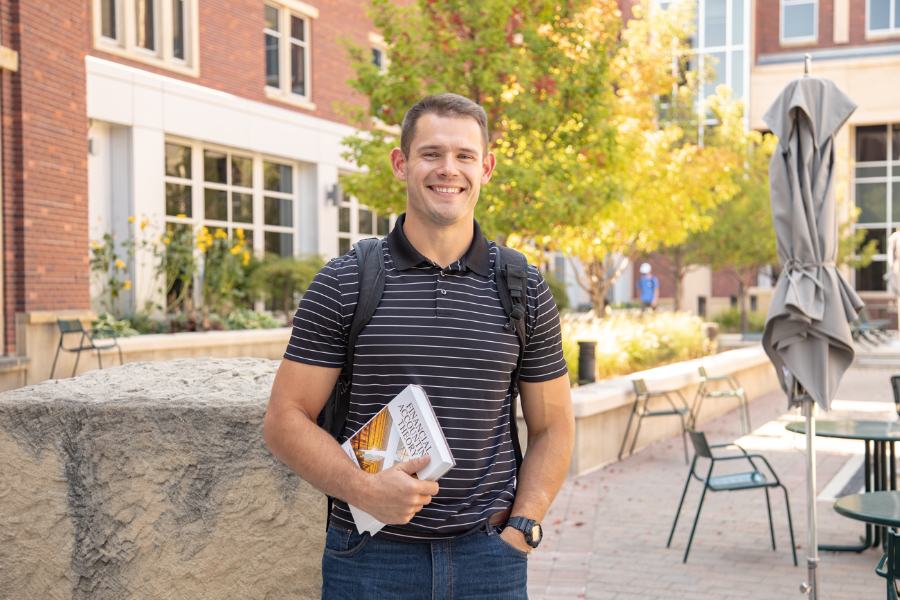 Mason Hampton stands outside of a brick building and holds a textbook.