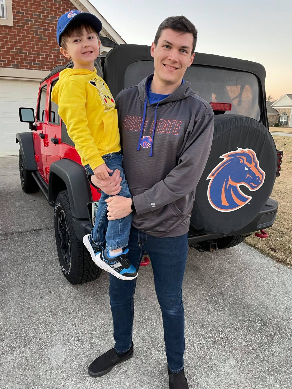 Austin Richardson poses with son in front of a house.