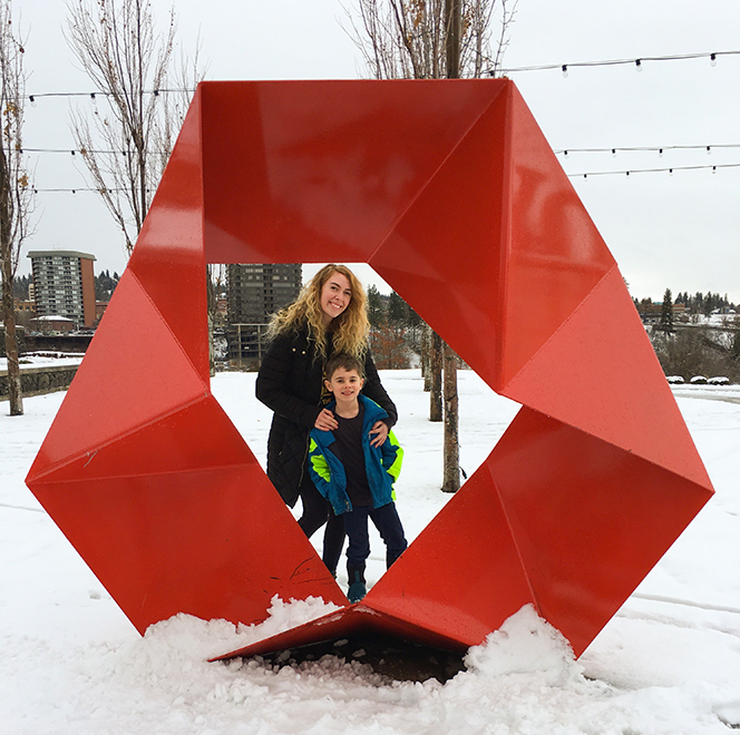 Meghan Howk and her son pose in the center of a red, oval-shaped sculpture.