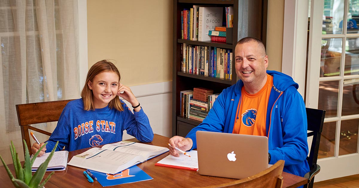 Father and daughter sitting side by side and working on school work together