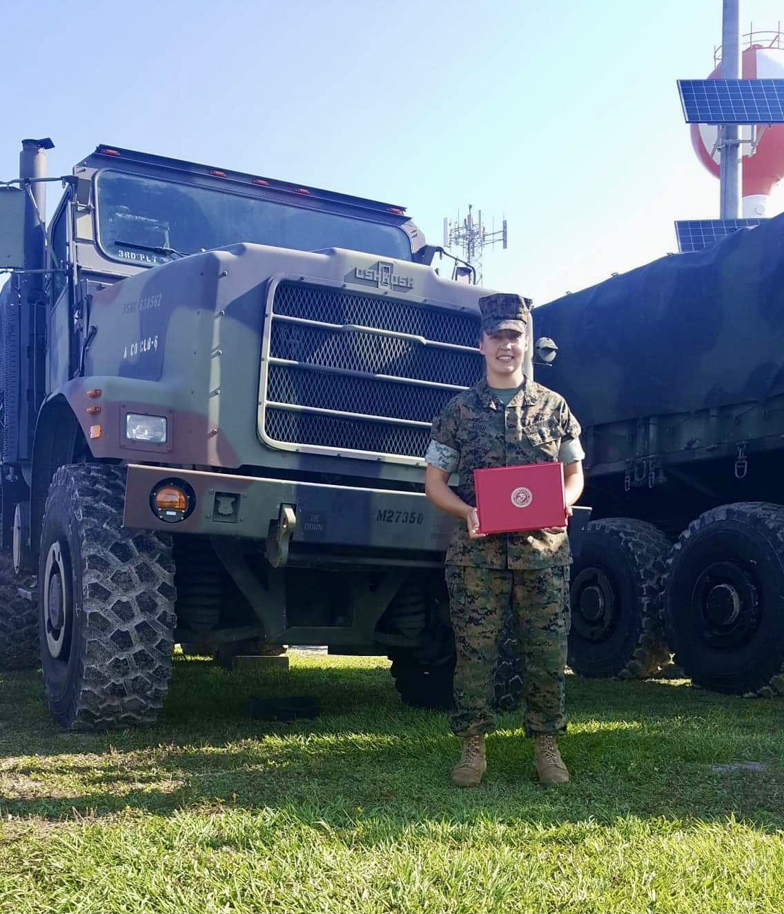 Brieann Jones poses in front of a military vehicle and holds an award.