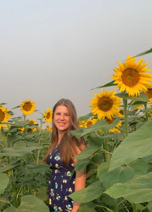 Kendra Patenburg in a field of sunflowers