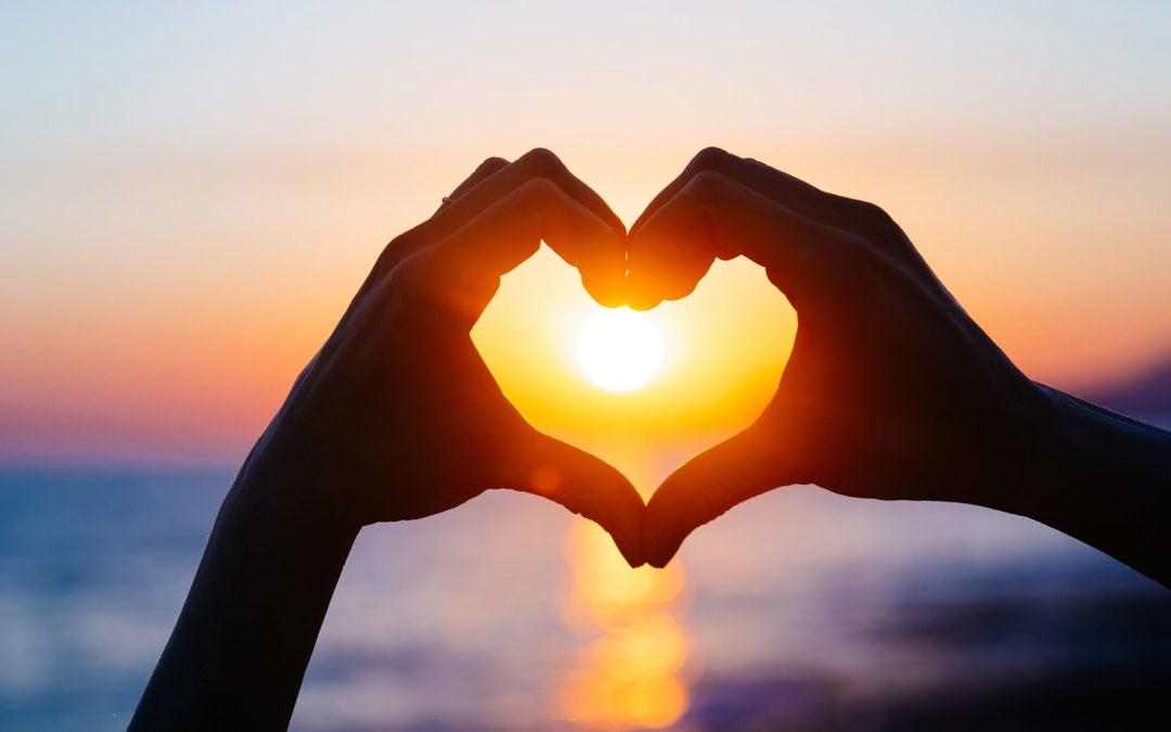Hands making a heart around a setting sun