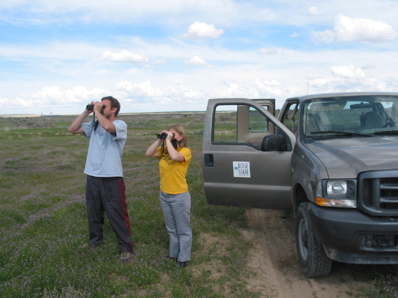 Two REU students using binoculars to survey for raptors