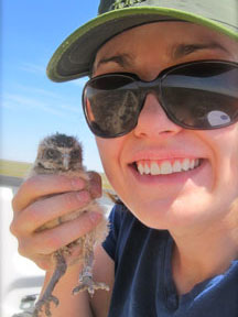 Jamie Wade holding a Burrowing Owl nestling in the field