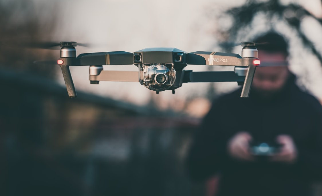 Drone flying with operator standing behind in soft focus.