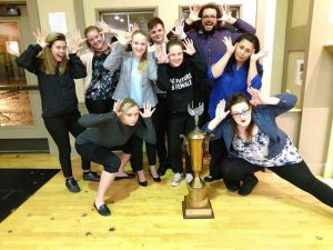 Social Work students pose around a trophy