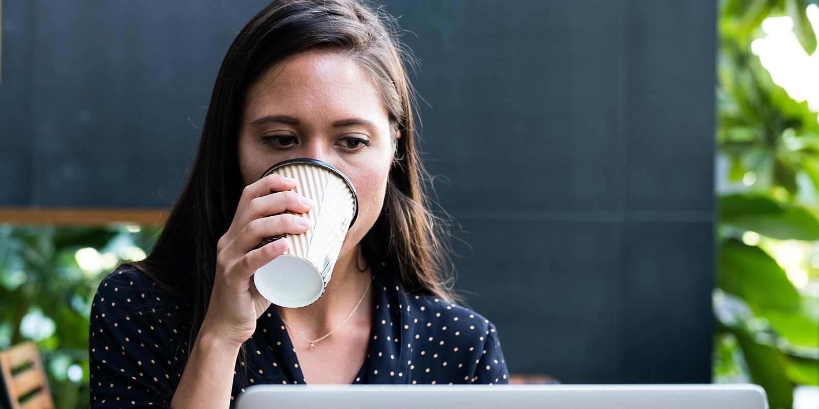 A woman drinking coffee while working at her laptop