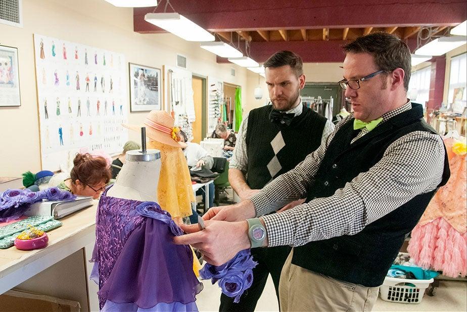 Two men adjust garment in theatre dressing room