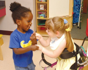 two little girls holding hands, one wearing a brace the other is not
